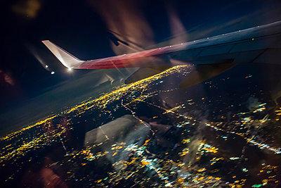 Airplaine approaching John F. Kennedy International Airport at night - p1057m1466825 by Stephen Shepherd