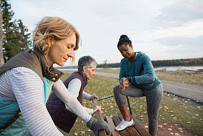 Women friends stretching preparing for running in autumn park - p1192m1194128 by Hero Images
