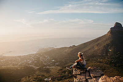 South Africa, Cape Town, Kloof Nek, woman sitting on rock at sunset - p300m2080820 by letizia haessig photography