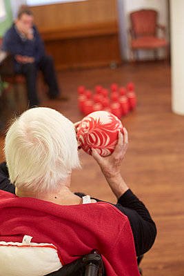 Age demented senior woman bowling with foam ball in a nursing home - p300m2219178 by Heinz Linke