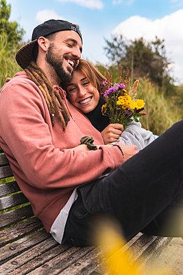 Happy woman embracing boyfriend on bench - p300m2281962 by Josu Acosta