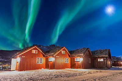 The Northern Lights (aurora borealis) and moon light up typical wood huts called Rorbu, Manndalen, Kafjord, Lyngen Alps, Troms, Norway, Scandinavia, Europe - p871m1478723 by Roberto Moiola