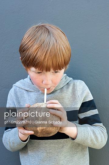 Child drinking coconut milk - p116m2278710 by Gianna Schade