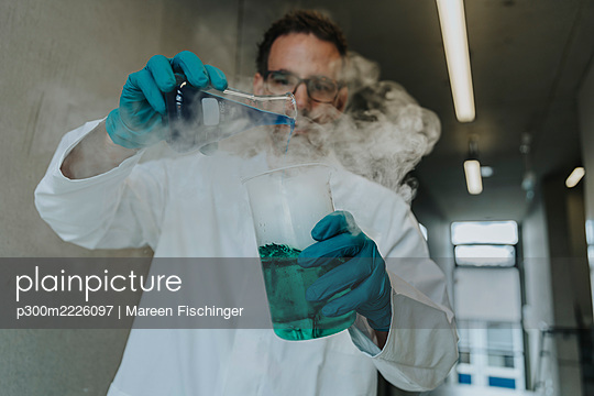Scientist mixing liquid solution in flask while standing at clinic corridor - p300m2226097 by Mareen Fischinger