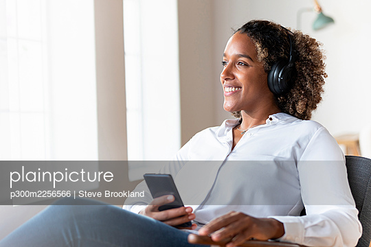 Woman wearing headphones looking away while sitting with mobile phone on armchair at home - p300m2256566 by Steve Brookland