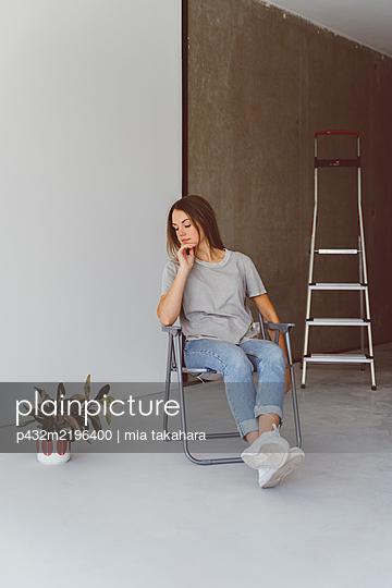 Junge Frau sitzt nachdenklich in Wohnung - p432m2196400 von mia takahara
