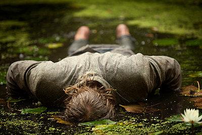 Man lying on swamp - p1166m985470f by Cavan Images