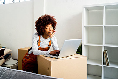 Afro woman with hand on chin day dreaming while standing by laptop in new loft apartment - p300m2251678 by Giorgio Fochesato