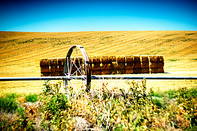 Agricultural Sprinkler and Hay Bales in Vast Field  - p694m2218856 by Justin Hill photography