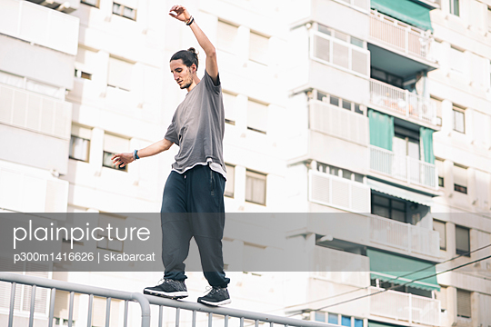 Young man doing Parkour in the city balancing on railing