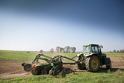 Tractor drilling field - p1026m1164186 by Patrick Frost