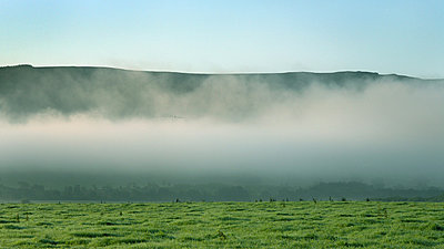 Hills, mist and green field - p1072m829034 by Graeme Ruddick