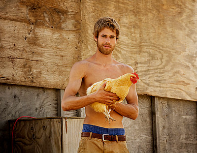Portrait of a young farmer holding a hen - p1166m968088f by Cavan Images