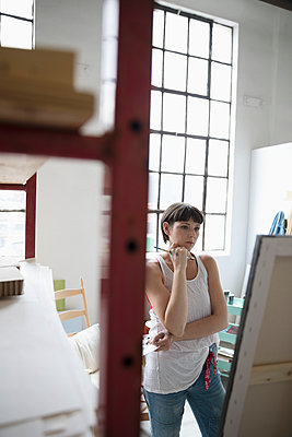Serious, pensive female painter examining canvas painting in art studio - p1192m1490234 by Hero Images