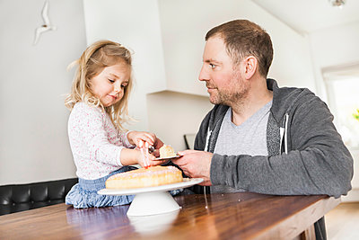 Father and daughter playing with doll's china set and piece of cake on plate - p300m2189118 by Floco Images