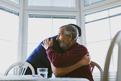 Caretaker embracing senior man at home - p426m1468232 by Maskot