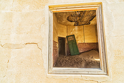 Sand in the rooms of a colourful and abandoned house; Kolmanskop, Namibia - p442m1086786 by Robert Postma