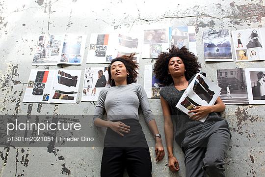 zwei Mädchen liegen mit Augen zu auf dem Boden - p1301m2021051 von Delia Baum