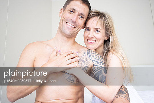Couple in love sitting on bed, portrait - p1640m2259577 by Holly & John