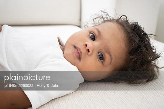 Multi ethnic toddler girl lying on the sofa - p1640m2260022 by Holly & John