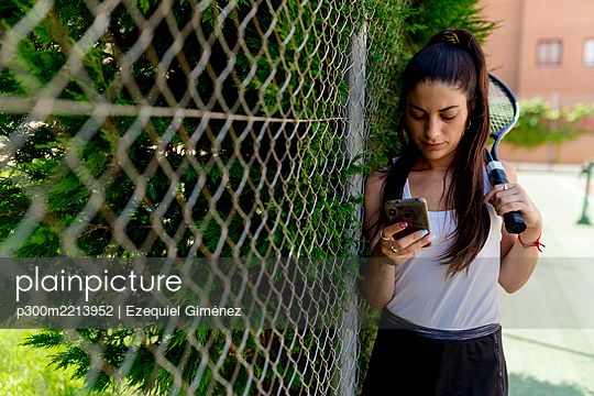 Female tennis player using smart phone while standing by fence in court - p300m2213952 by Ezequiel Giménez