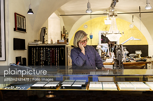 Goldsmith taking phonecall at counter of her store - p352m2121478 by Folio Images