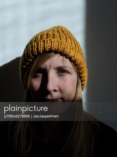 Portrait of a young woman wearing a yellow wool hat - p795m2278566 by JanJasperKlein