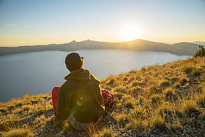 Rear view of hiker looking at view while sitting on mountain during sunset - p1166m1415115 by Cavan Images