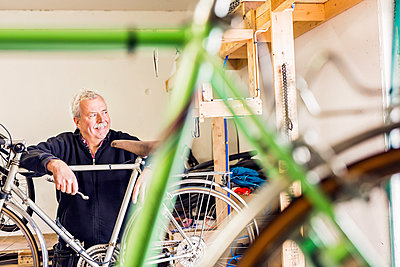 Thoughtful senior repairman leaning on bicycle in workshop - p1264m1122174f by Astrakan