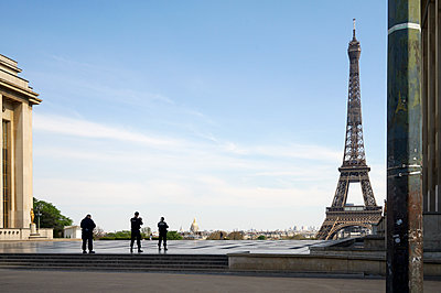 Eiffel tower deserted by covid 19 with 3 policemen walking - p1610m2181517 by myriam tirler