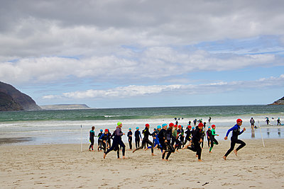 Triathlon, runners on the beach - p1640m2246789 by Holly & John