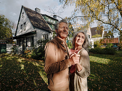 Happy senior couple in garden of their home in autumn - p300m2156211 by Gustafsson