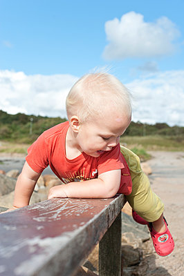 Cute boy playing on bench - p312m1147525 by Rebecca Wallin