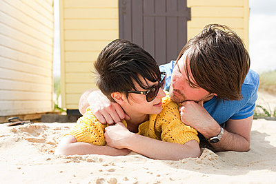 Young couple by a beach hut - p9247097f by Image Source