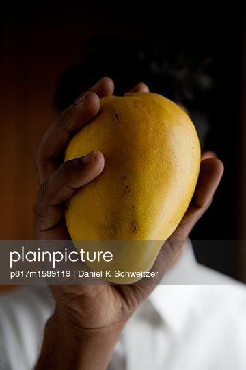 Mann hält eine frische Mango - p817m1589119 von Daniel K Schweitzer