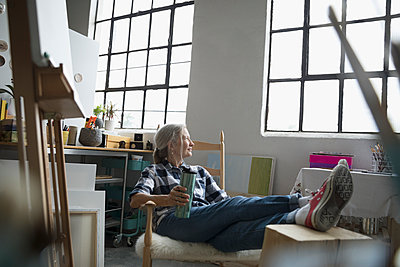 Female painter relaxing with feet up, drinking tea and looking out window in art studio - p1192m1490264 by Hero Images