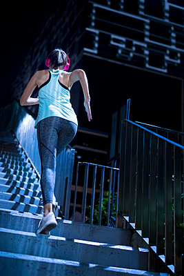 Young woman with pink headphones running upstairs in modern urban setting at night - p300m1536179 by Steve Brookland