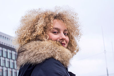 Portrait of smiling blond woman with ringlets wearing fur collar - p300m2070396 by Linda Meyer