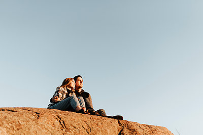 Clear sky over young couple sitting together on rocky surface during autumn hike - p300m2241250 by Sara Monika