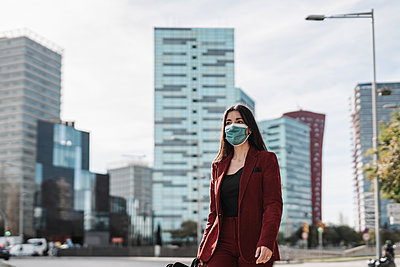 Businesswoman in red blazer wearing protective face mask while walking in city during COVID-19 - p300m2265920 by COROIMAGE