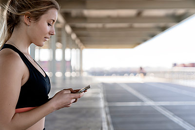 Young female athlete using smart phone - p300m2273598 by Albert Martínez