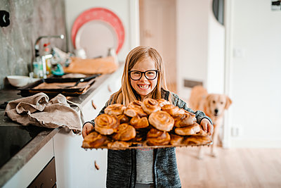 Smiling girl holding tray with cinnamon buns - p312m2237421 by Anna Johnsson