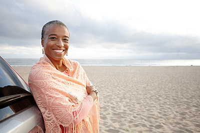 Black woman in shawl standing on beach - p555m1479244 by Peathegee Inc