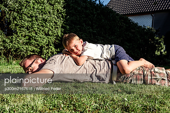 Portrait of barefoot little boy relaxing on his father's back in the garden - p300m2167618 by Wilfried Feder