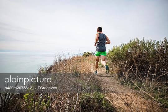 Runner jogging on cliff top, Santa Barbara, California, USA - p429m2075312 by JFCreatives
