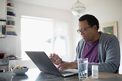 Senior man using laptop at kitchen counter - p1192m1529730 by Hero Images