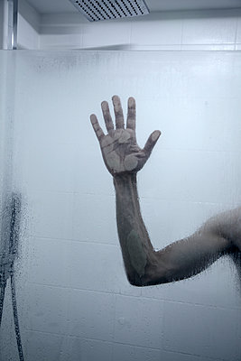 Mans Hand Against Screen in Shower - p1248m2076344 by miguel sobreira