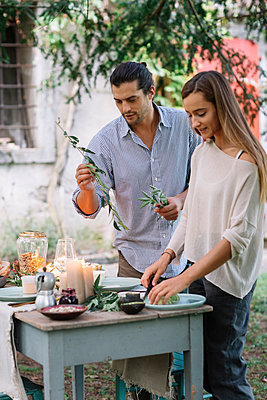 Couple preparing a romantic candelight meal outdoors - p300m2068829 by Alberto Bogo