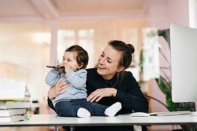 Junge Geschäftsfrau mit Tochter im Büro - p586m1451946 von Kniel Synnatzschke