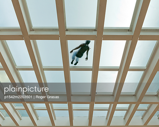 Young woman lying on a glass roof - p1542m2203501 by Roger Grasas